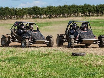 Two off-road buggies racing on a grass track