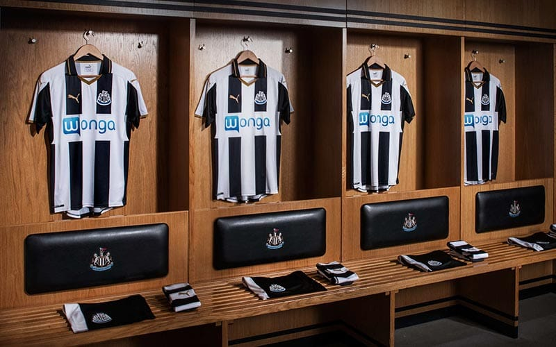 Image of Newcastle United changing room with four shirts hung up, and shorts and socks sat in front.
