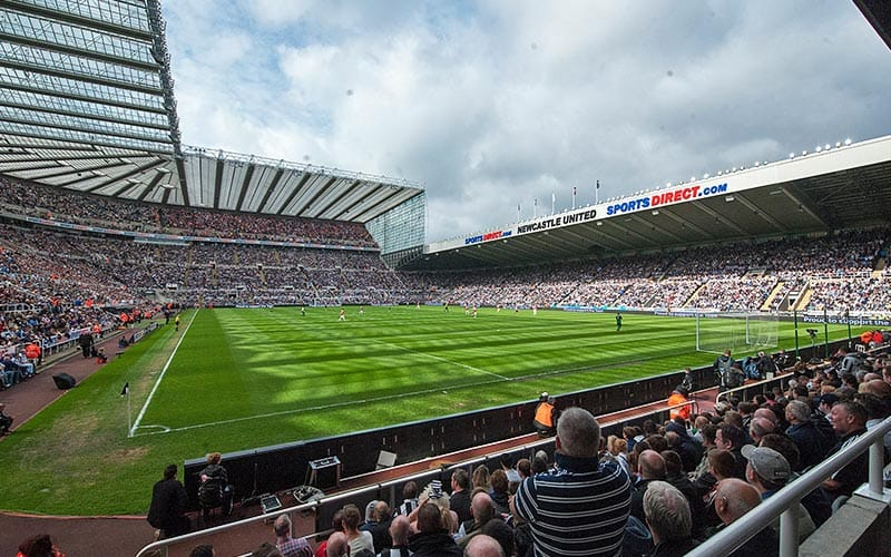 Image of St James' Park pitch from the corner of the stadium with the crowd all sat in their seats and the sky full of clouds.