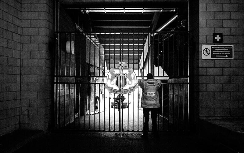 Black and white image of gate with Newcastle United Crest in the centre and a steward with his back to the camera.