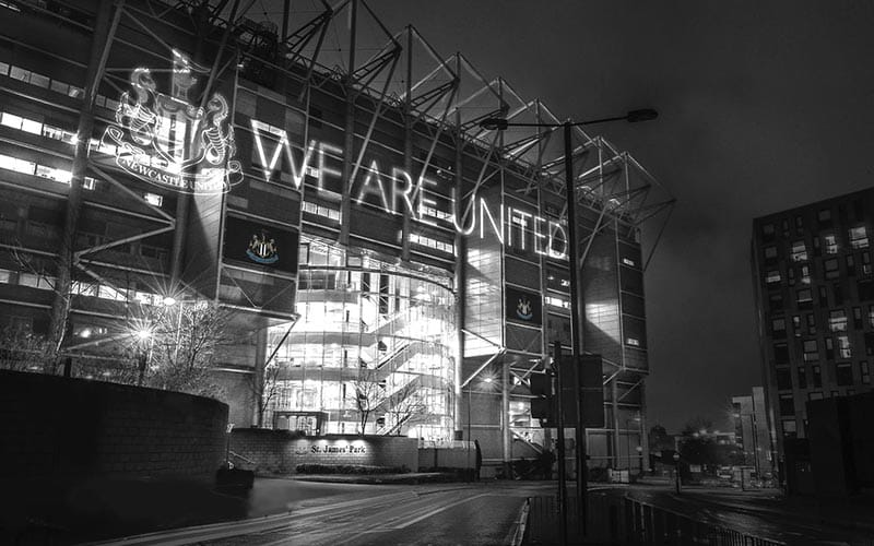 Image of the side of St James' Park with We are United and the crest projected onto the side.