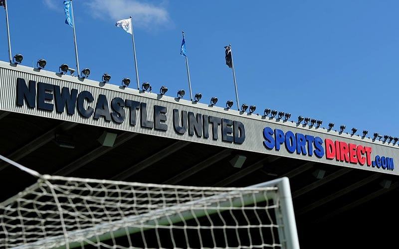 Top of football net at front of image, with Newcastle United on top of stand in background, in front of a clear blue sky.