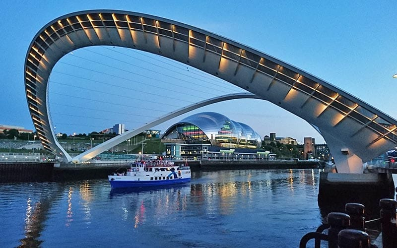 Boat passing under the Millenium Bridge on the River Tyne with the Sage in the background.