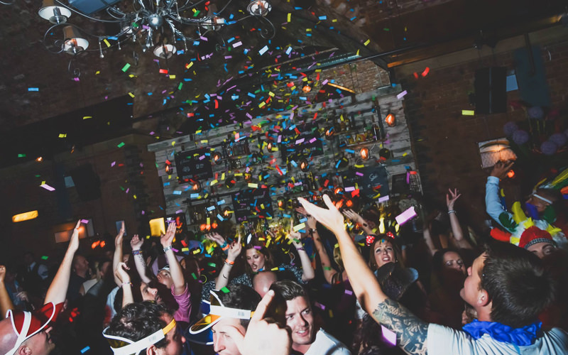 A group of people dancing in a nightclub while confetti falls from the ceiling