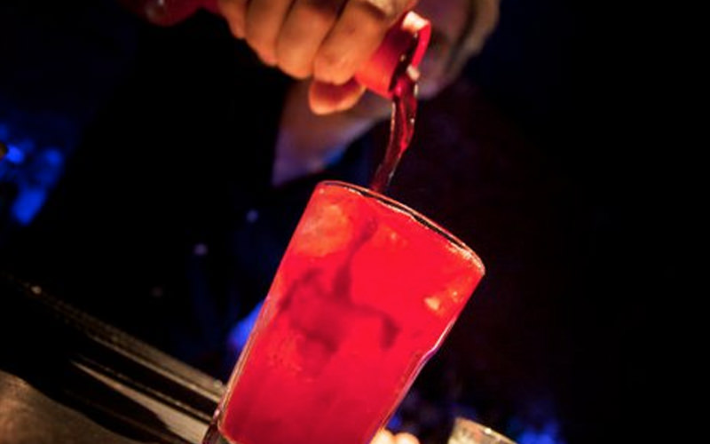 A barman making a cocktail in a nightclub