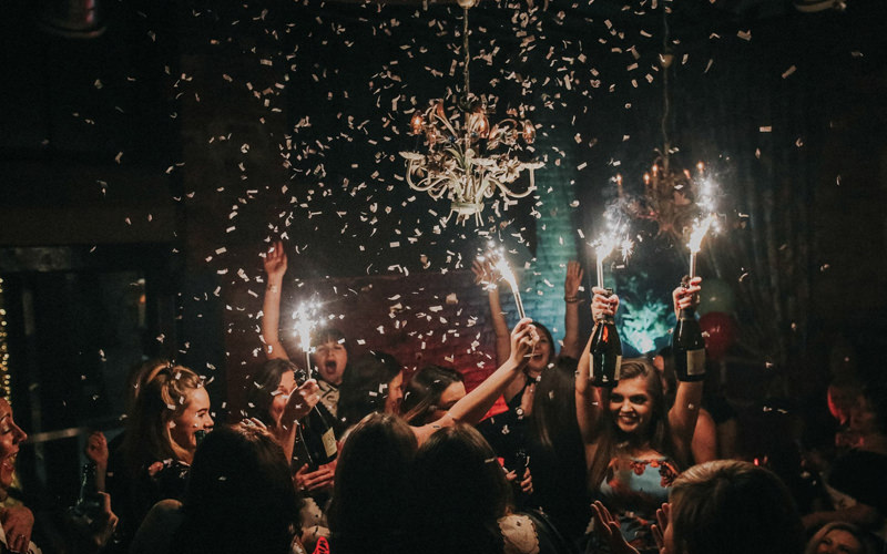 A group of people holding sparklers while dancing in a nightclub