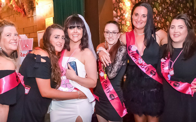 A group of women wearing sashes in a nightclub