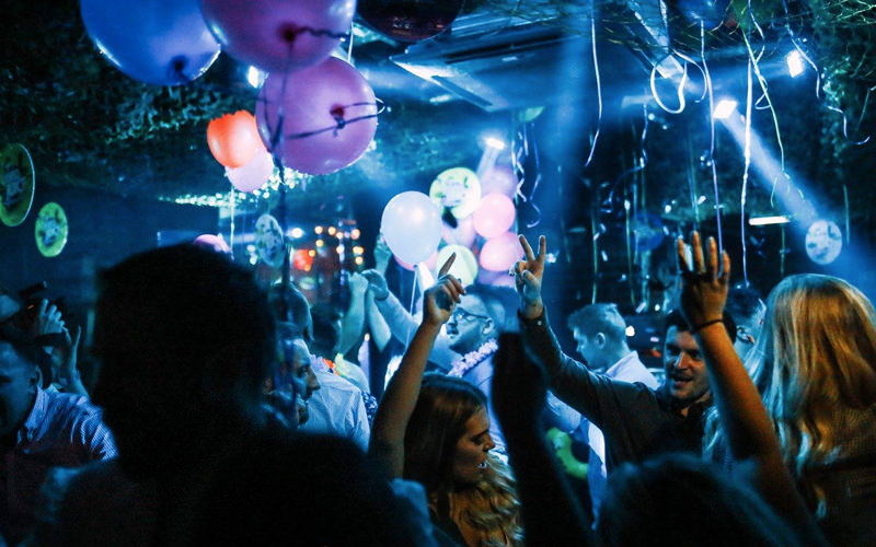 A group of people dancing in a nightclub surrounded by balloons