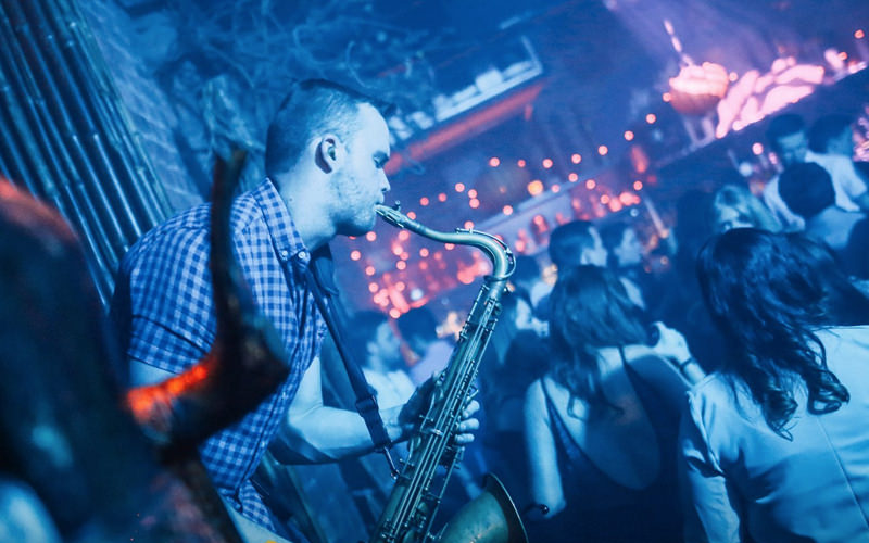 A man playing a saxophone in a nightclub