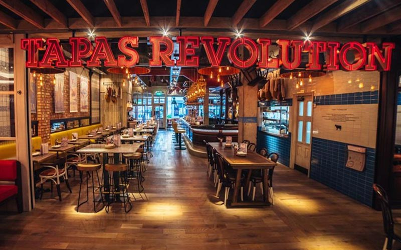 A room with wooden tables and chairs and the Tapas Revolution sign above