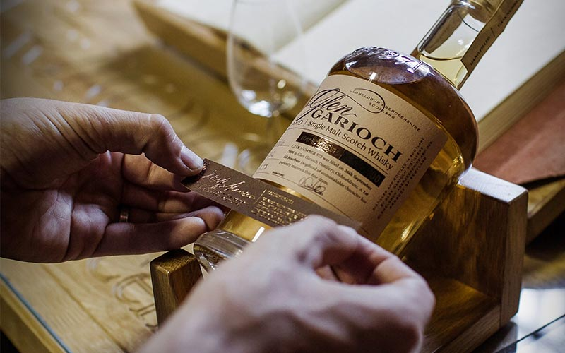 A close up of a label getting placed onto a bottle of Glen Garioch