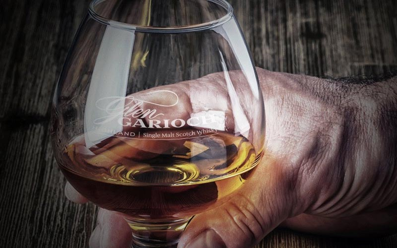 A close up of a hand holding a glass of Whiskey