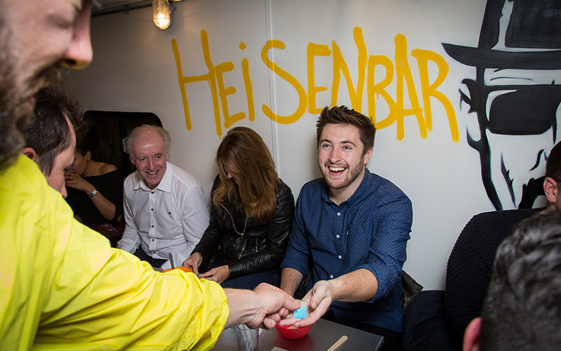 Some people in Heisenbar with the name graffitied across the wall in yellow spray paint