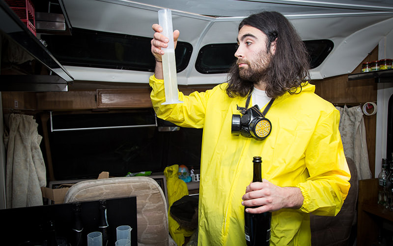 A man wearing a yellow overall and holding a science beaker