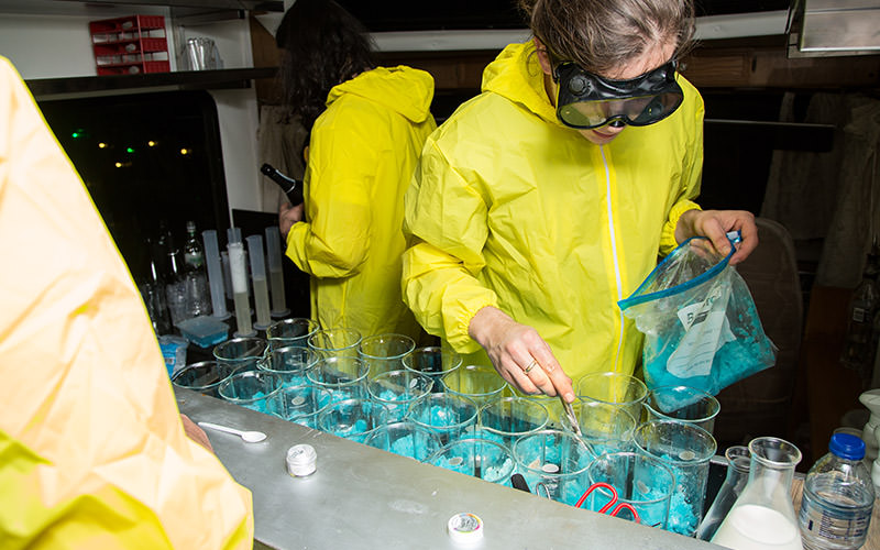 Some people wearing high-viz lab jackets in a lab
