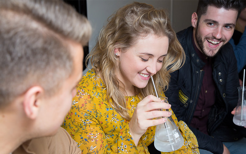Two men looking at a girl drinking a cocktail