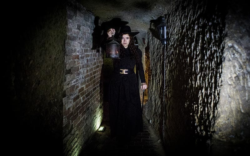 Two people dressed up, down an eerie corridor of the goal