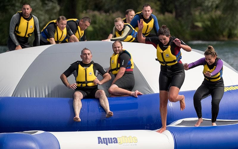 Some people in wetsuits on an inflatable water course