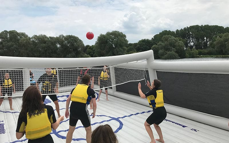Some people playing volleyball on a wet inflatable