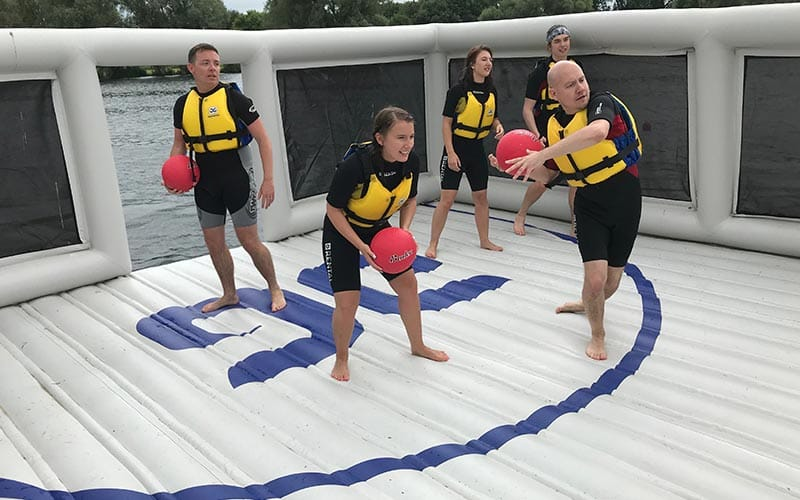 Some people holding balls on an inflatable course