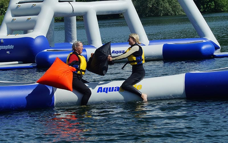 Some people playing pole joust on an inflatable in the water