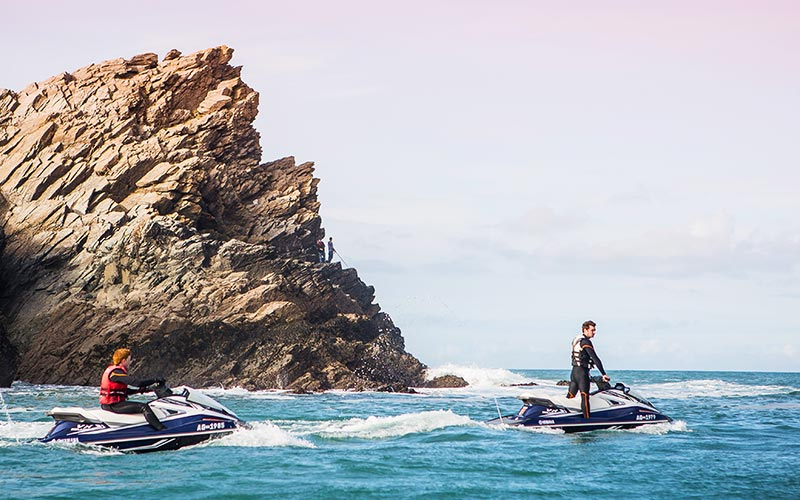 Two people on jet skis with a cliff in the distance