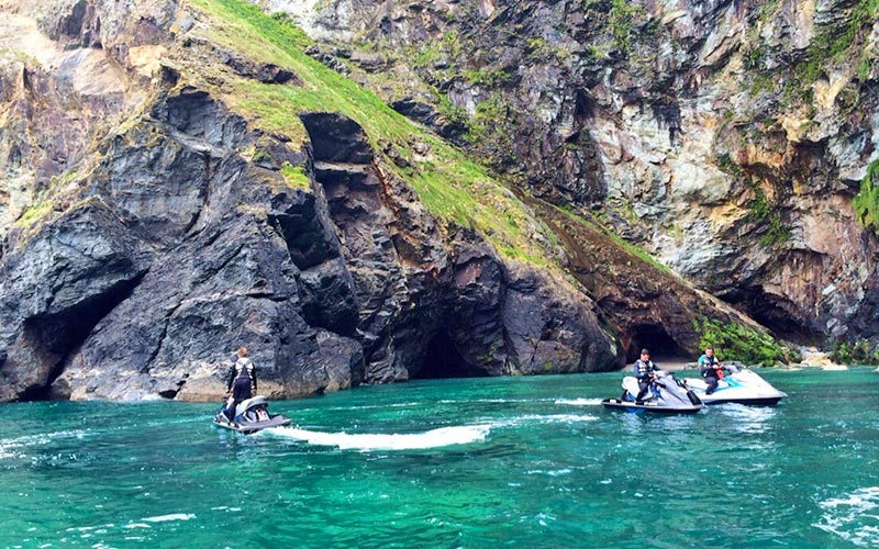 A group of people on jet skis with a cliff in the distance