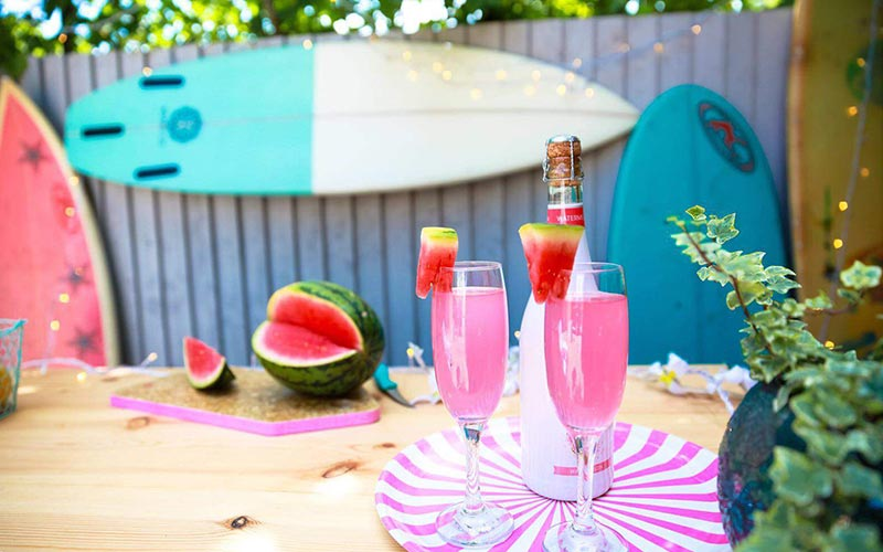 Two glasses of pink alcohol on a tray and a watermelon in the background