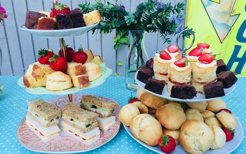 A selection of cakes and sandwiches on tiered trays