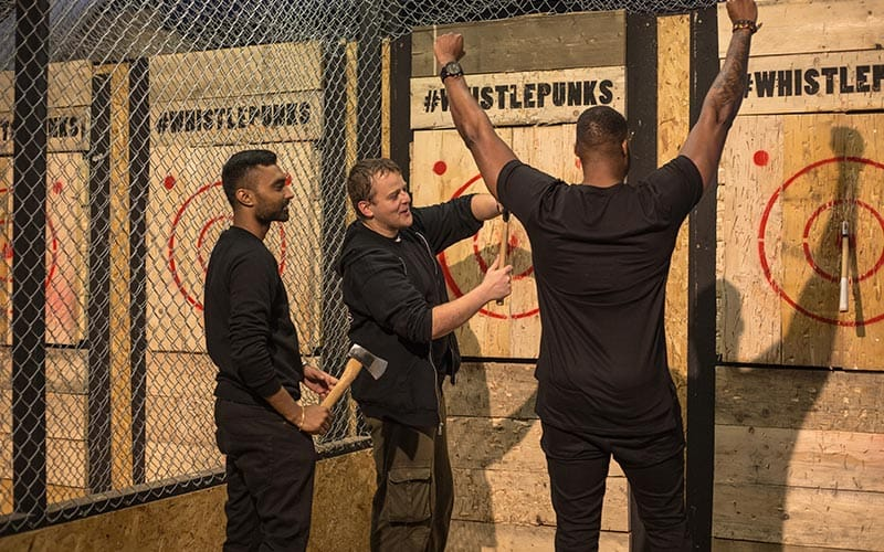 Image of three men standing next to target boards with axes inside the target lines