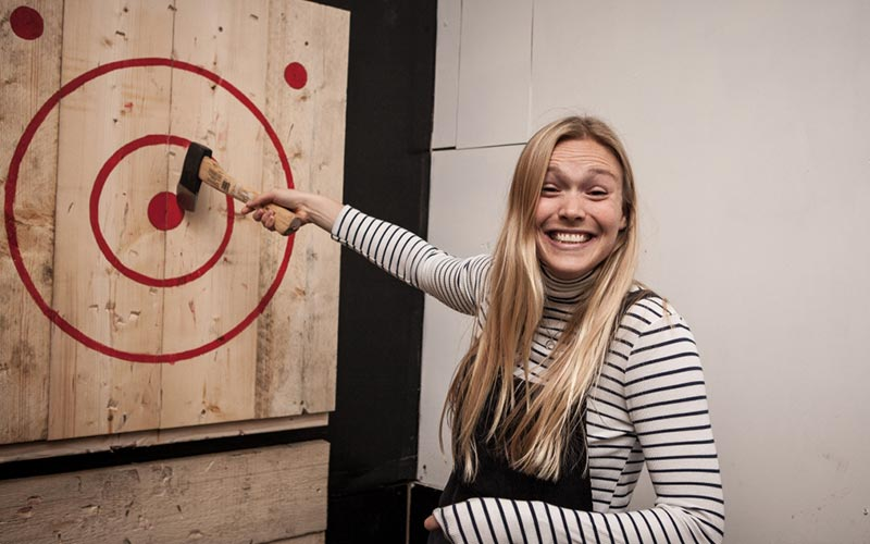 A woman smiling and pointing to an axe in the bullseye of a target