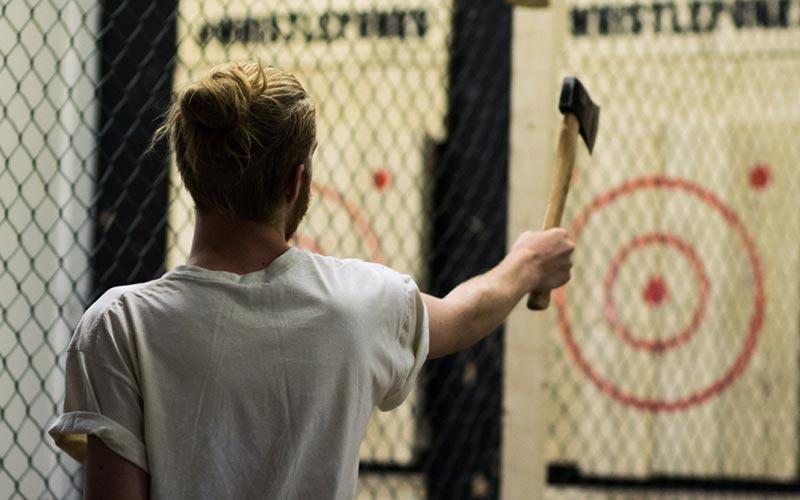 A man aiming an axe at a target