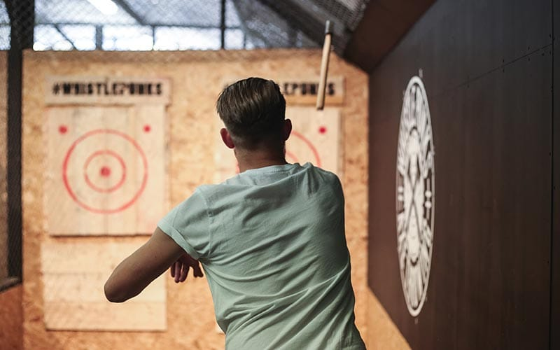 Image of a man throwing an axe at the target on the wall