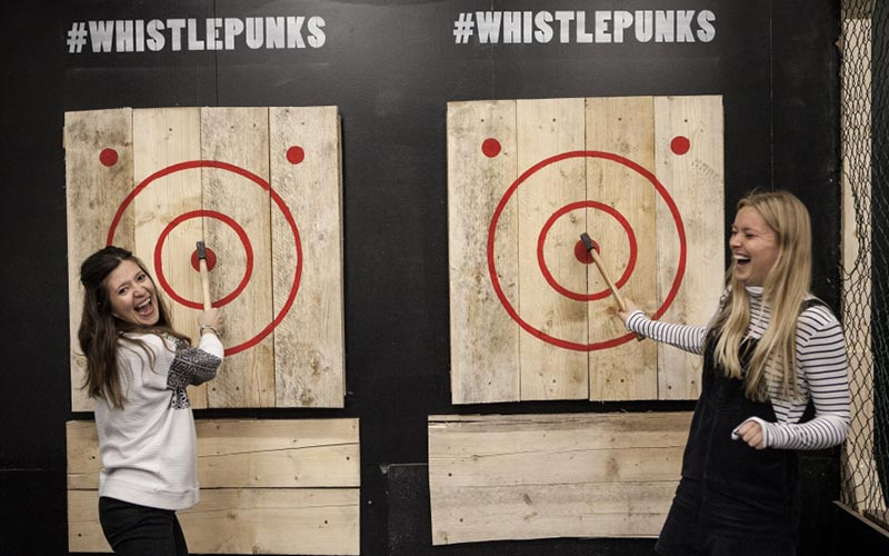 Two girls next to targets with axes sticking out of them