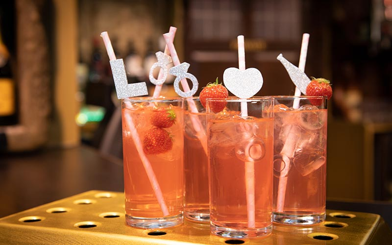 Glasses of alcohol with straws on a bar