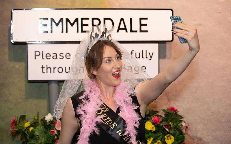 A girl dressed in a pink feather boa and a bride veil, in front of the Emmerdale sign
