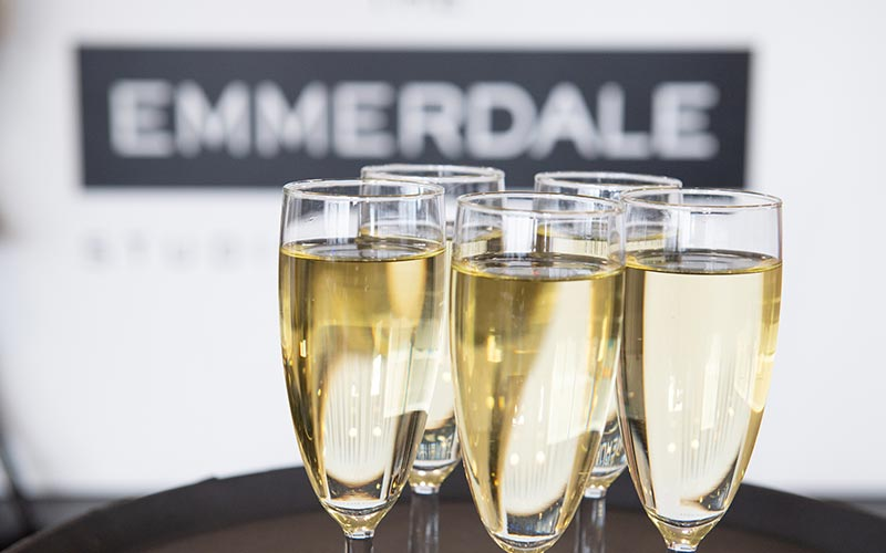Five glasses of champagne in front of an Emmerdale sign