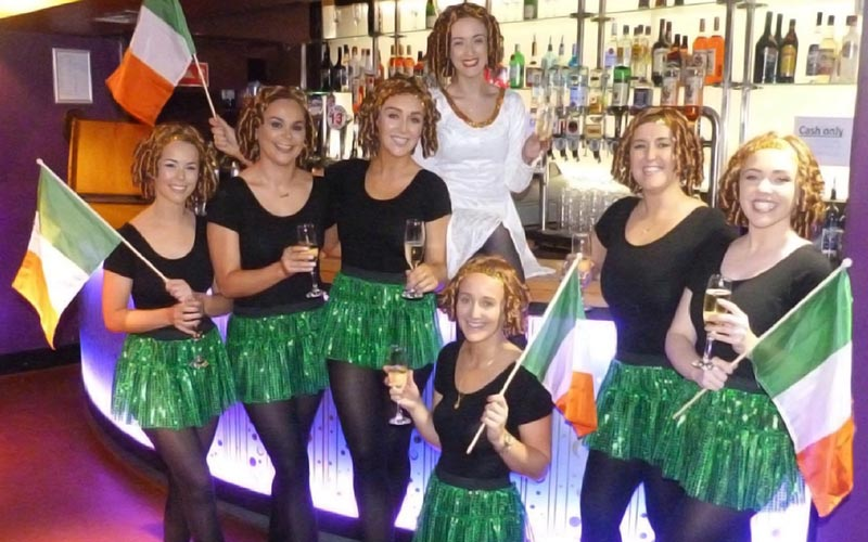 A group of girls in Irish dance outfits, in front of a bar