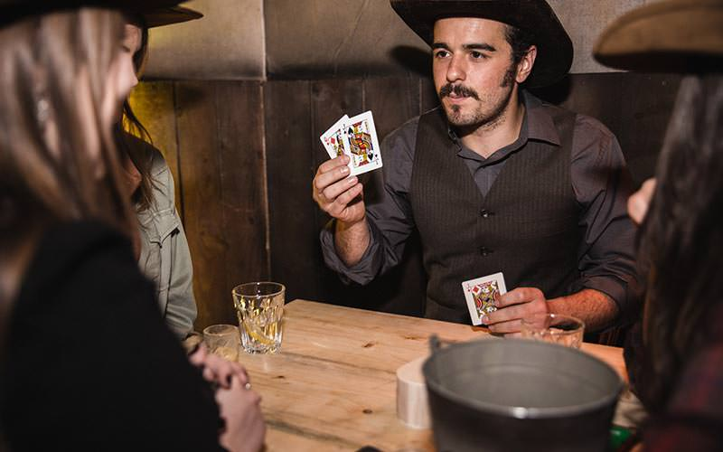 A man dressed as a cowboy playing with cards at a wooden table in the Moonshine Saloon