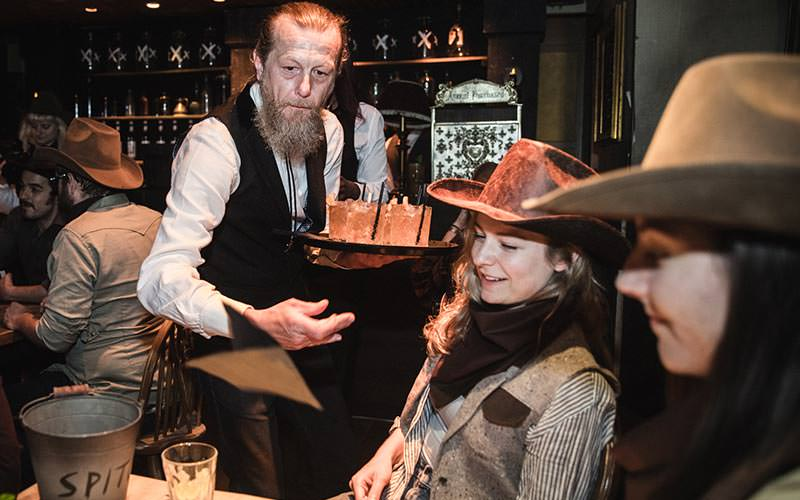 A waiter serving people drinks in the Moonshine Saloon