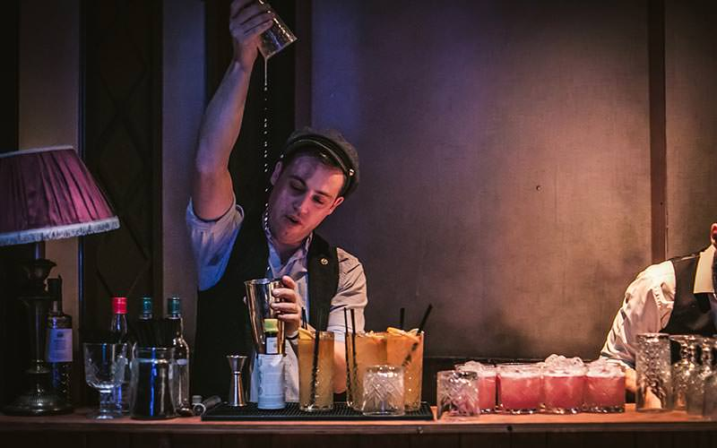 A bartender making drinks in the Moonshine Saloon
