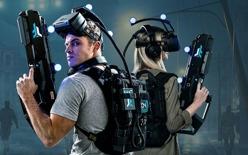 Two people wearing VR helmets and posing with guns