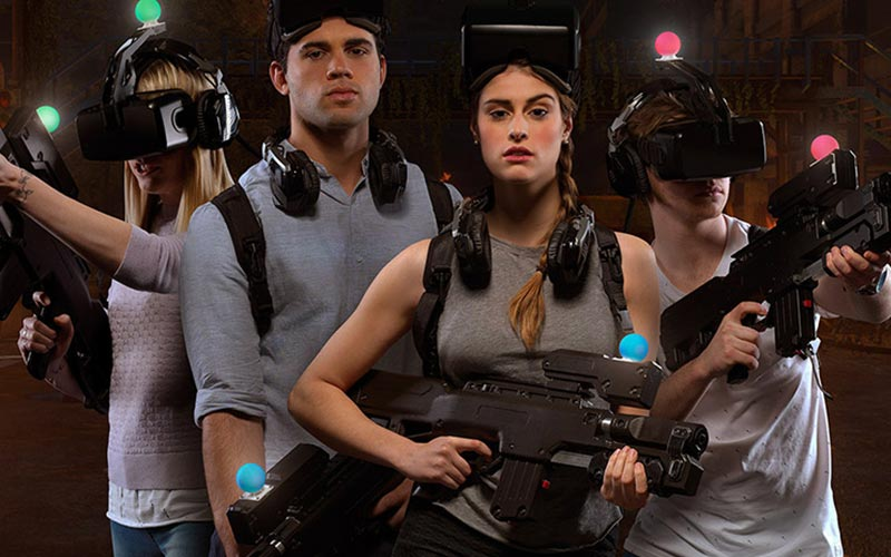A group of people wearing VR helmets and posing with guns