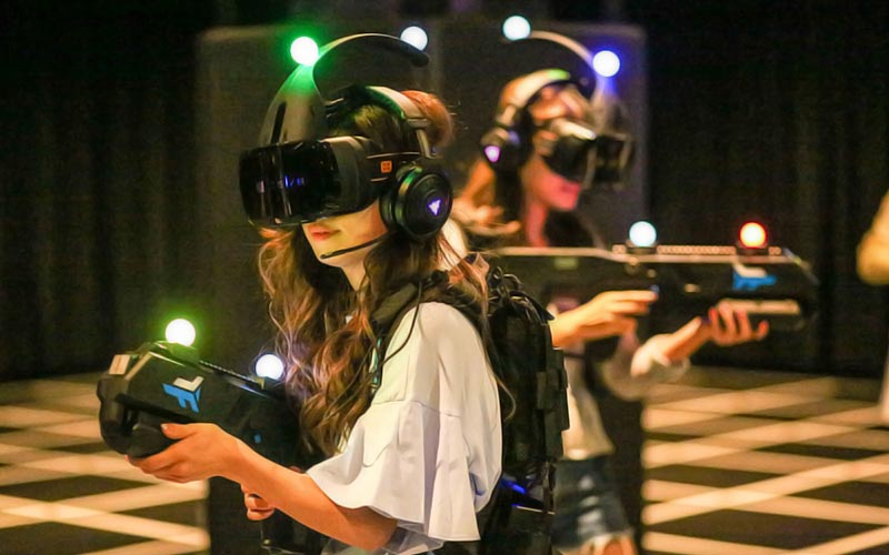 Two people in a room wearing VR helmets and posing with guns