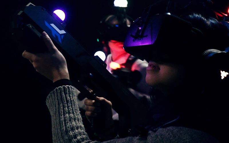 A close up of a girl wearing a VR helmets and holding a gun