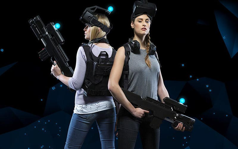 Two women wearing VR helmets and posing with guns