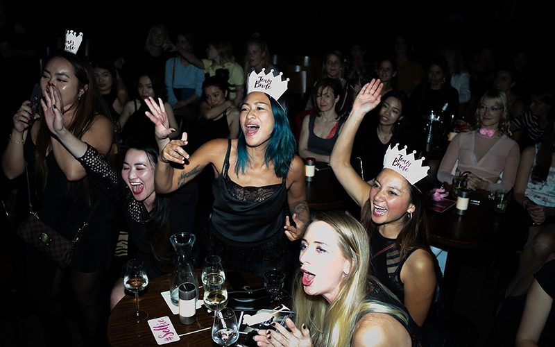 A group of women wearing hen party hats dancing while watching strippers