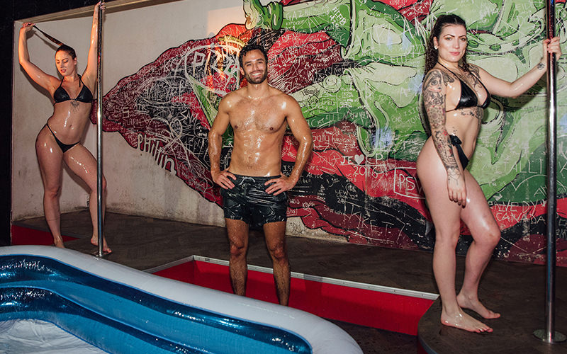 Two women and a man covered in oil standing in front of an inflatable pool