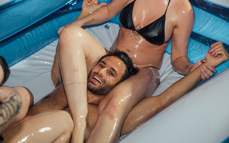 Two women wrestling a man covered in oil in an inflatable pool