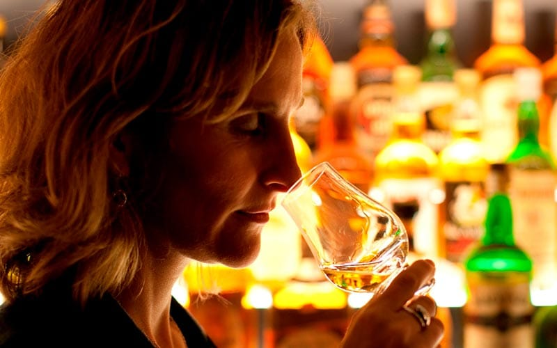 Image of a woman standing at the bar smelling a glass of whiskey